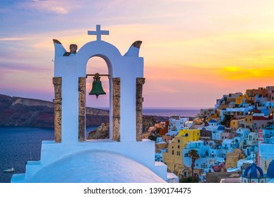Arch with a bell, white houses and church  in Oia at dusk golden sunset, island Santorini, Greece.