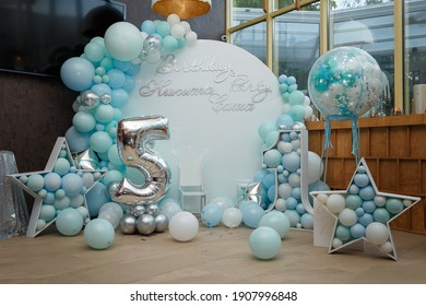 Arch of blue balloons for boy happy birthday party. Number 5 and 1 for two brothers. Festive decorative elements, photo zone with star. Inscription Nikita, Sasha.