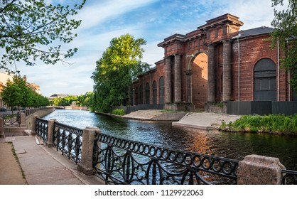 Arch of the brick building of New Holland in St. Petersburg on the bank of the Moika River on a summer sunny morning