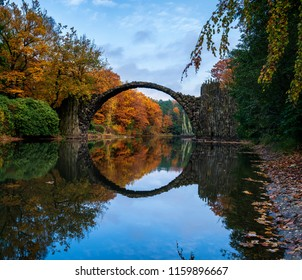 Arch Bridge in Kromlau, Saxony, Germany. Colorful autumn in Germany. Rakotz bridge in Kromlau