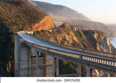 Arch bridge on winding coastal road next to Big Sur state park in sunset light with mountains and ocean cliff on pacific cost. Cabrillo highway. California.