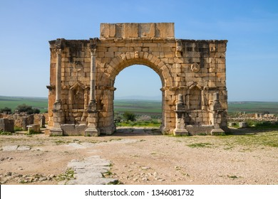Arch of Caracalla (Triumphal Arch) at the Archaeological Site of Volubilis under a blue sky, Fes-Meknes, Morocco.