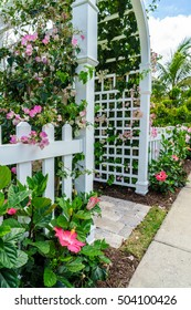 Arch covered with colorful flowers, entrance to the house. Naples FL, USA