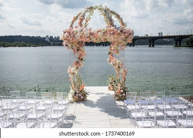 Arch covered with flowers for a wedding ceremony on the background of the lake. Wedding set up with beautifil flowers, outdoor