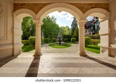 An arch with an exit to a lawn with the fountain