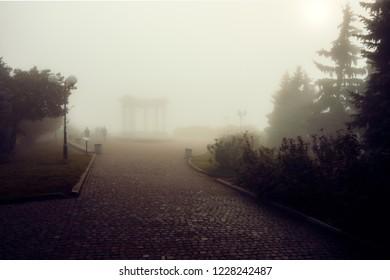 Arch of Friends in Poltava, Ukraine deem image in the fog.