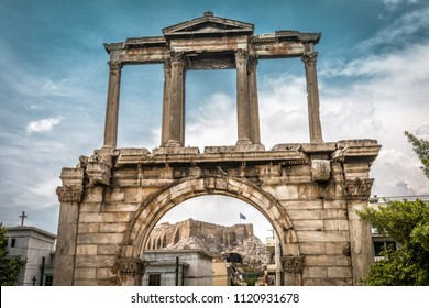 Arch of Hadrian or Hadrian's Gate, Athens, Greece. It is one of the main landmarks in Athens. Famous Acropolis of Athens in the distance. Scenic vintage view of the ancient Greek monument in Athens.