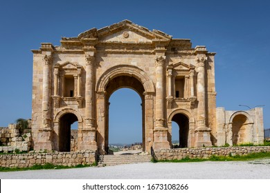 Arch of Hadrian at the roman ruins of Jerash, Jordan. Front view on a sunny day with blue sky. It features some unconventional, possibly Nabataean, architectural features, such as acanthus bases.