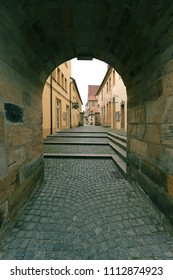 Arch passage on a small old street  with a cobblestone and the walls  are lined with stone limestone, ancient Bavarian city - Bayreuth, Upper Franconia, Bavaria, Europe, Germany, vertical town image