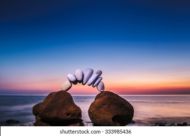 Arch of pebbles between of stones on the seashore