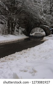 Arch and road in mountains in winter forest, Hungary. Medieval arch in mountain. Road in winter snowfall. Snowy highway in forest. Road architecture. Traffic road through mountain. Travel concept.