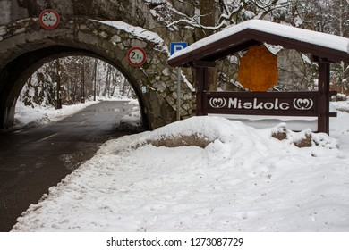 Arch and road in mountains in winter forest, Miskolc, Hungary. Miskolc road sign and medieval arch in mountain. Road in winter snowfall. Snowy highway. Road architecture. Traffic through mountain.