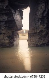 "Arch of rocks with reflection in water. Beach of ""Las Catedrales"" in Gijon (Spain)"