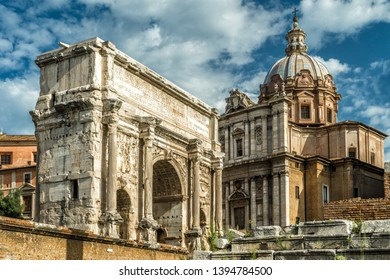 Arch of Septimius Severus and old church on Roman Forum in summer, Rome, Italy. Ancient Forum is one of the top landmarks in Rome. Vintage view of the famous antique architecture in the Rome center.