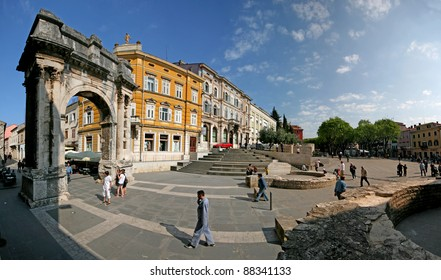 Arch of the Sergeii on Portarata square with people passing.