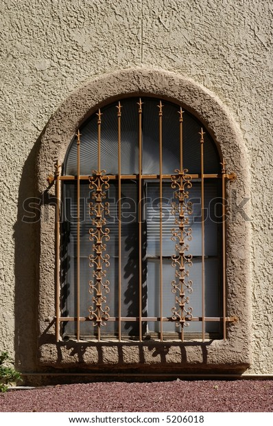 Arch shaped stone window with metal bars.