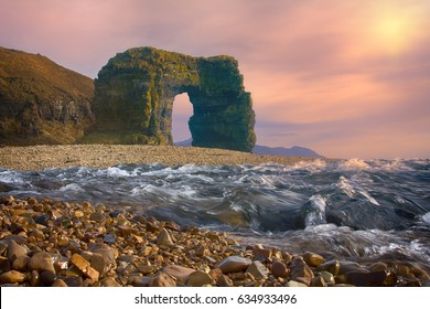 Arch of Steller (in honor of zoologist Georg Steller). Massive stone arch on shore of Pacific ocean. Bering Island. Commander Islands rock formation