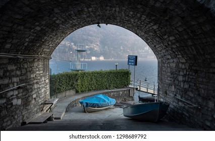 The arch of a stone tunnel in Moltrasio, Italy, leading to a boat landing on Lake Como. Translation of the blue sign: Pro-Moltrasio Association, Private jetty, Boarding and disembarkation