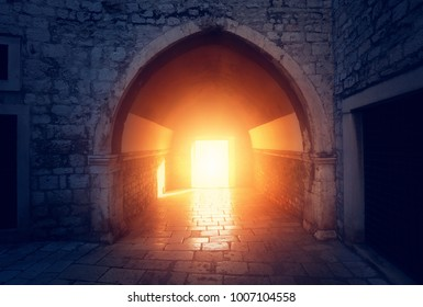 Arch and sunlight at the end. Photo of medieval building