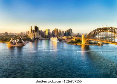 Arch of the Sydney Harbour bridge across Sydney harbour to The Rocks and Circular quay waterfront of city CBD lit by soft morning light between blue waters and sky.