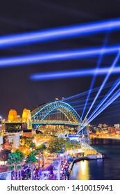 Arch of the Sydney Harbour bridge under blue laser lights of Vivid Sydney ligth show over the Rocks waterfront and Harbour.