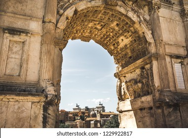 Arch of Titus framing the beautiful ancient city of Rome. Intricate White Marble Honorific Arch carved on the Via Sacra southeast of the Roman Forum.