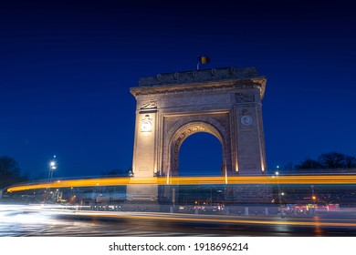 Arch of Triumph (Arcul de Triumf) building in Bucharest Romania during the evening with traffic lights at bottom of it