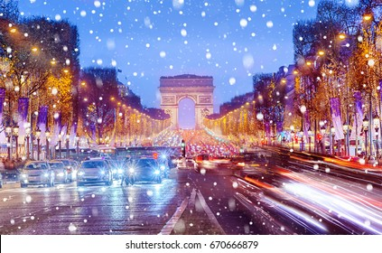 Arch of Triumph and Champs Elysees in Paris at Christmas snowy night, France.