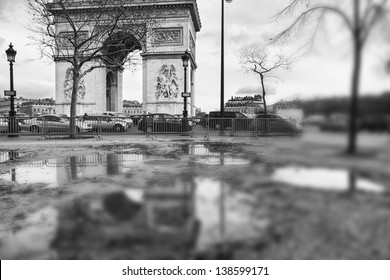 Arch of Triumph on Place de l'Etoile in Paris, France, reflecting in a big puddle on the sidewalk