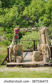 Arch for the wedding ceremony of burlap and wooden logs decorated with flowers and hay on wooden pier