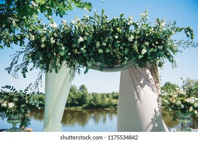 Arch for the wedding ceremony. Arch, decorated with beautiful fresh flowers and cloth.  Registration at the place of marriage. Wedding arch of real flowers. Night