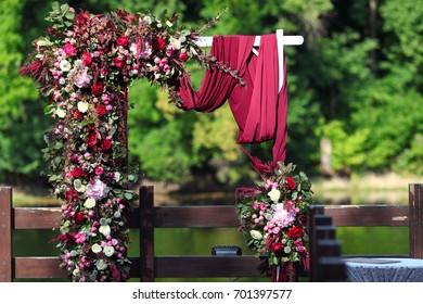 Arch for the wedding ceremony. Arch, decorated with beautiful fresh flowers and cloth. Bordeaux color. Registration at the place of marriage. Wedding arch of real flowers