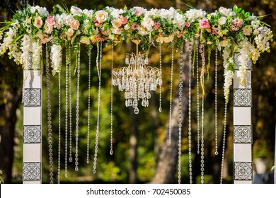 Arch for the wedding ceremony. Decorated with crystal chandelier and fresh flowers. Wedding decorations. The newlyweds.
