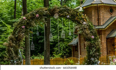 Arch for the wedding ceremony. Decorated with fabric flowers and greenery. Is located in a pine forest. Background church. Wedding decorations in rustic style. Just married. Wedding decor.