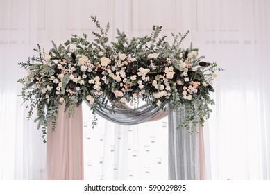 Arch for the wedding ceremony. Arch decorated with peachy and silvery cloth and flowers