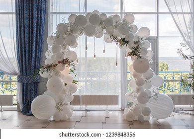 an arch of white balloons . festive decor for the wedding. decor of balloons and lights. wedding background. place of the wedding ceremony