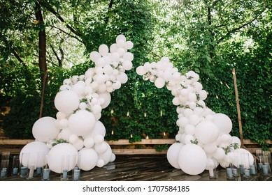 Arch of white wedding balloons with greenery Decor.