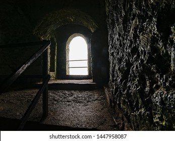 Arch window in old fortified Hell Fire club hunting logs in Dublin, Ireland , view from inside with bright light shining on thick granite walls