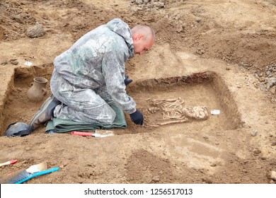 Archaeological excavation. Archaeologist in a digger process. Hands with tools, conducting research on human bones (tomb), part of skeleton and skull in the ground, shovel, brush. Outdoors, close up.