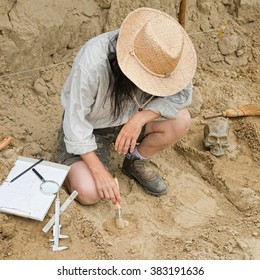 Archaeological excavation - Archaeologist revealing and documenting objects from past