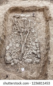 Archaeological excavation. Human remains (bones, skeleton and skull) in the half-ground, with little artefacts close in the tomb. Outdoors, copy space.