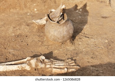 Archaeological excavations. Human remains (bones of skeleton legs/foot) in the ground, with artefacts found in the tomb (damaged ceramic jar). Real digger process. Outdoors, copy space, close up.