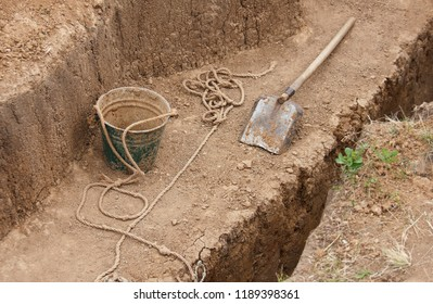 Archaeological excavations. A shovel on the ground next to a bucket and a rope.  Excavations. things of the archaeologist.