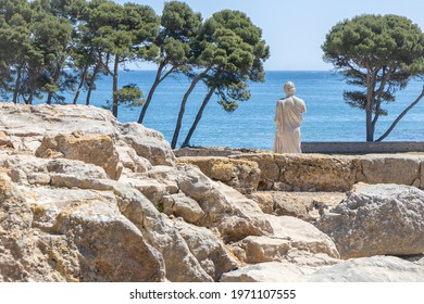 Archaeological Remains of ancient city Empuries with reproduction of the statue of Aesclepius on the remains of a Greek rampart. Archaeology Museum of Catalonia, Spain.  - Shutterstock ID 1971107555