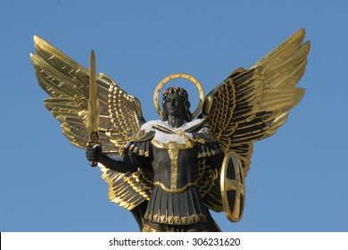 Archangel Michael Sculpture at Independence Square (Maidan Nezalezhnosti, Khreschatyk), Kiev, Ukraine. Gold plated bronze statue  isolated against a blue sky.