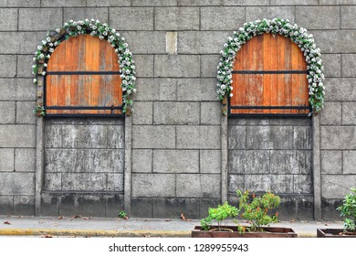 Arched boarded up windows with wooden shutters-white roses garlands-concrrete masonry units or CMUs wall facing General Luna St.-stop for e.trikes covering the whole Intramuros-Inner Walled City area.