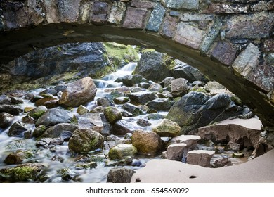 Arched Bridge Over Rocky Flowing Stream