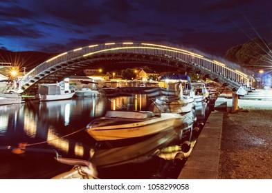 Arched bridge for pedestrians in Trogir, Croatia, Unesco. Night scene. Travel destination. Boats in the port. Yellow photo filter.