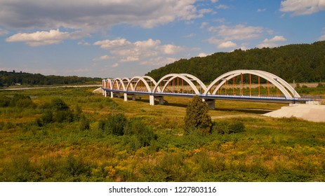 Arched bridge with seven white arches in the valley.