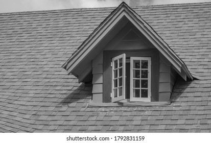 Arched Cottage Roof With Open Attic Window.  Monochrome photograph of a restored old wood cottage for use as a background.